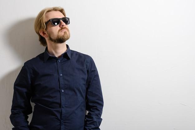 Attraktiver mann im blauen hemd und in der sonnenbrille, die nahe einer weißen wand stehen