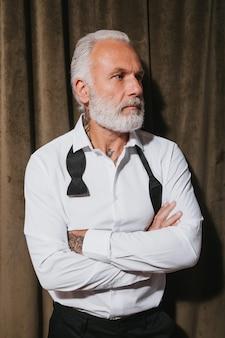 Attraktiver mann im weißen hemd posiert auf samtwand