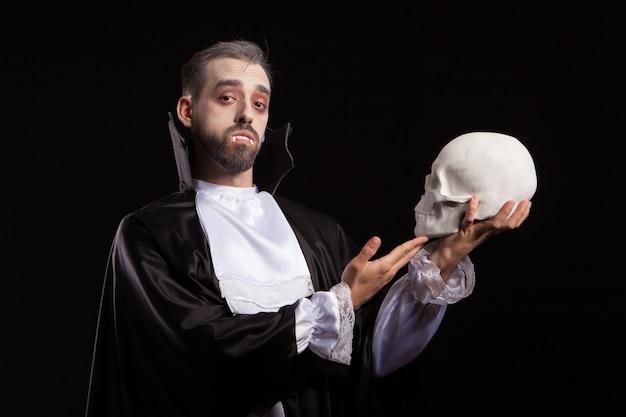 Attraktiver mann in dracula-kostüm und vampir-theet mit einem menschlichen schädel. mann im halloween-kostüm. mann im monsterkostüm.