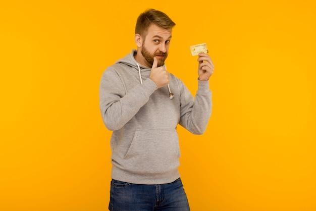 Attraktiver mann in einem grauen hoodie zeigt mit einem finger auf die kreditkarte, die in seiner hand auf gelb hält
