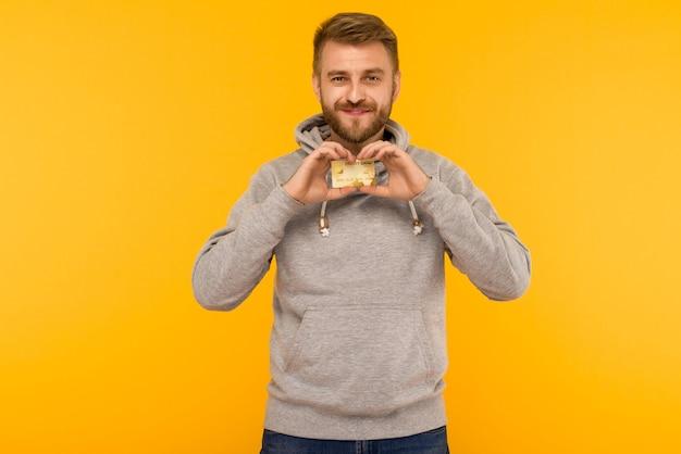 Attraktiver mann in einem grauen kapuzenpulli hält eine kreditkarte in seinen händen auf einem gelben hintergrundbild