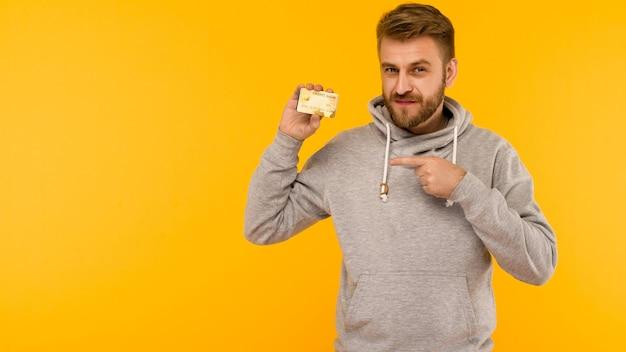 Attraktiver mann in einem grauen kapuzenpulli zeigt mit einem finger auf die kreditkarte, die in seiner hand auf einem gelben hintergrundbild hält