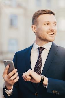 Attraktiver mann kommt auf das treffen mit dem kunden und betrachtet uhr und hält intelligentes telefon