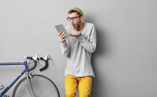 Attraktiver mann mit ansprechendem aussehen, gekleidet in stilvolle kleidung, mit großer überraschung auf dem tablett aussehend, während er eine nachricht von seinem freund oder verwandten mit unangenehmen nachrichten erhält. männlicher radfahrer