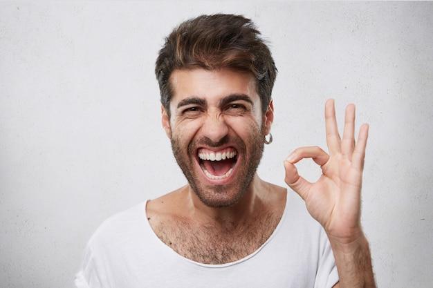 Attraktiver mann mit bart, der seine augen schließt und den mund mit freude öffnet, das ok zeichen zeigt, das froh ist