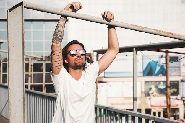 Attraktiver mann mit der sonnenbrille, die heraus in der stadt hängt