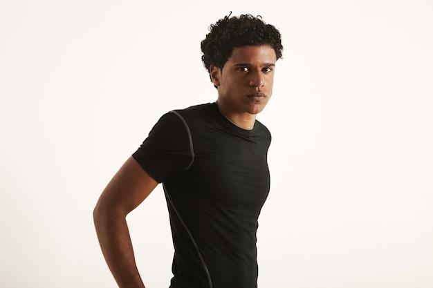 Attraktiver mann mit einem afro, der ein schwarzes technisches synthetisches t-shirt mit händen auf dem rücken trägt