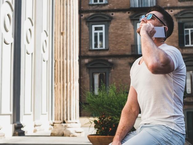 Attraktiver mann mit einem telefon auf dem hintergrund von hellem