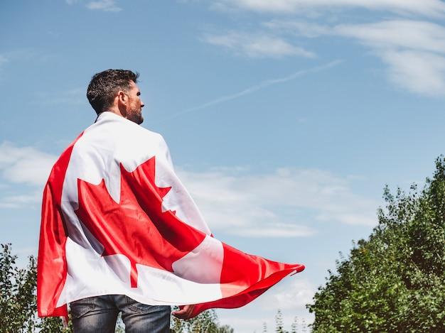 Attraktiver mann mit kanadischer flagge auf blauem himmelshintergrund an einem klaren, sonnigen tag. ansicht von hinten, nahaufnahme. nationalfeiertagskonzept