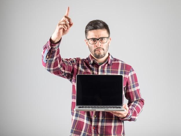 Attraktiver mann mit leerem laptop, der seinen zeigefinger zeigt