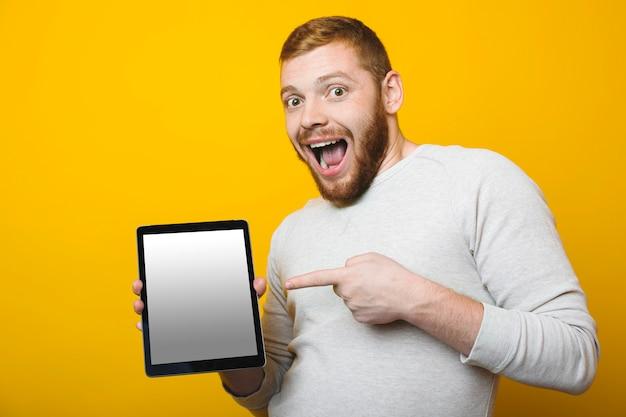 Attraktiver mann mit rotem bart, der auf moderne tablette mit leerem display zeigt a