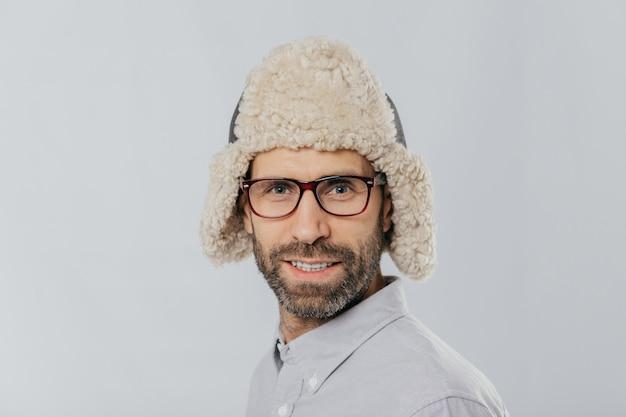 Attraktiver mann mit stoppeln, trägt brille und pelzmütze