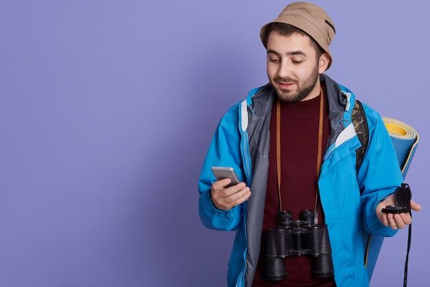 Attraktiver mann touristischer rucksacktourist, der internetanwendung auf modernem smartphone verwendet und mit matte, fernglas und rucksack aufwirft