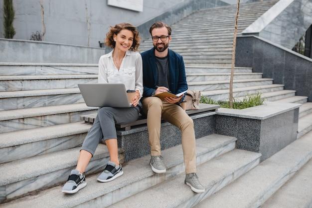 Attraktiver mann und frau, die auf treppen im städtischen stadtzentrum sitzen