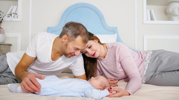 Attraktiver mann und frau, die süßes schlafendes baby im schlafzimmer betrachten.