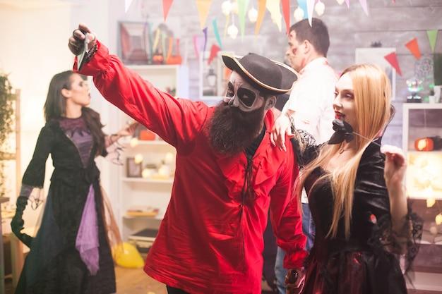 Attraktiver mann und frau, die wie pirat und vampir verkleidet sind und ein selfie auf der halloween-party machen.
