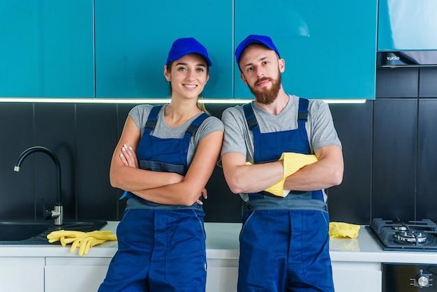Attraktiver mann und hübsche frau in arbeitskleidung, die in der zeitgenössischen küche mit waschmitteln vor der kamera posiert