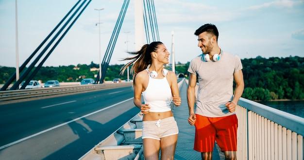 Attraktiver mann und schöne frau, die zusammen auf der brücke joggen