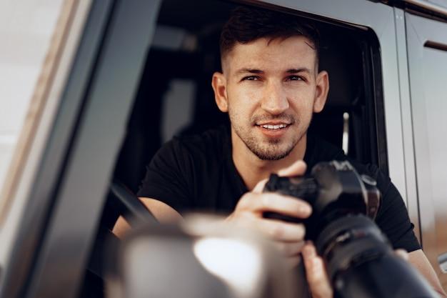 Attraktiver mannfotograf, der ein foto macht, während er in seinem auto sitzt