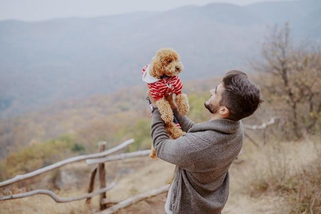 Attraktiver mischlingsmann, der seinen liebenden hund hält, während er im herbst in der natur steht.