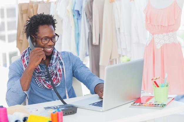 Attraktiver modedesigner, der am telefon spricht