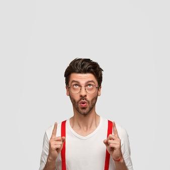 Attraktiver modischer typ mit trendiger frisur, rundem mund, zeigt mit beiden zeigefingern nach oben