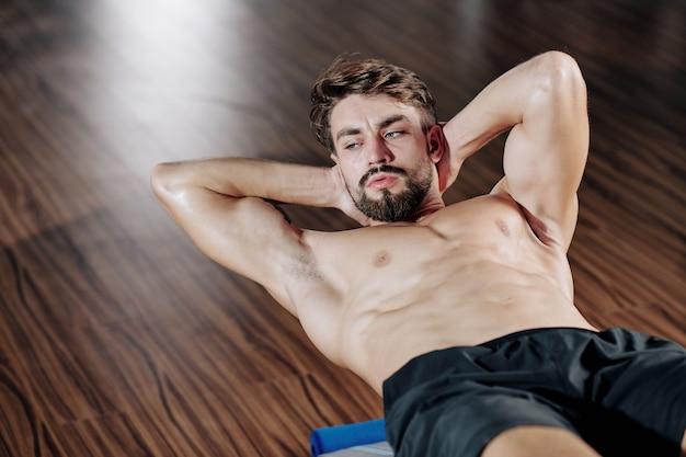Attraktiver muskulöser bärtiger junger mann, der sit-ups auf bank im fitnessstudio tut Premium Fotos