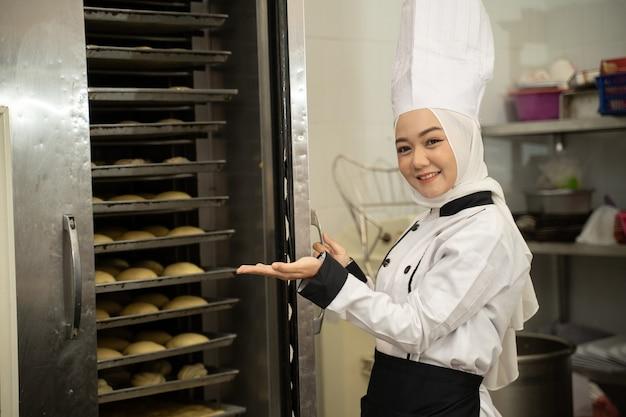 Attraktiver muslimischer bäcker, der in die kamera in der küche der bäckerei mit großem ofen lächelt