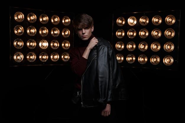 Attraktiver mysteriöser junger stilvoller mann in einer schwarzen jacke in einem roten modischen golf, der in der dunkelheit drinnen vor dem hintergrund der leuchtend orange vintage-glühbirnen aufwirft. stilvolles model