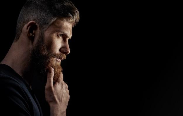 Attraktiver nachdenklicher junger bärtiger mann untersucht den abstand
