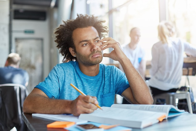 Attraktiver nachdenklicher junger männlicher student im tagträumen des blauen t-shirts während der arbeit an der hauptaufgabe im coworking cafe, schreiben der komposition, vorbereiten für englisch oder literatur, nachdenkliches aussehen