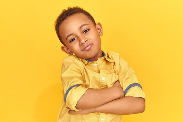 Attraktiver niedlicher kühler afroamerikanischer kleiner junge gekleidet im gelben hemd, das arme auf seiner brust kreuzt und kamera mit freudigem lächeln betrachtet, haltung, die vertrauen ausdrückt