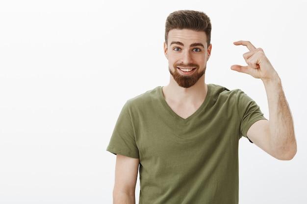 Attraktiver optimistischer bärtiger sportler in olivgrüner t-shirt-form, kleines oder winziges objekt, das von wenig anstrengung bis zum ziel erzählt und breit mit sicherem und selbstbewusstem ausdruck über der weißen wand lächelt