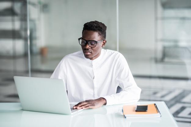 Attraktiver positiver fleißiger junger büroangestellter, der am schreibtisch vor offenem laptop sitzt