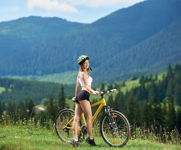 Attraktiver radfahrer der jungen frau, der nahe gelbem fahrrad auf einer ländlichen spur in den bergen steht