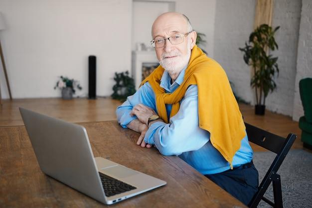 Attraktiver reifer bärtiger geschäftsmann in seinen sechzigern, der drahtlose hochgeschwindigkeits-internetverbindung auf generischem tragbarem computer verwendet, der im modernen innenraum des heimbüros sitzt. menschen, alter und technik