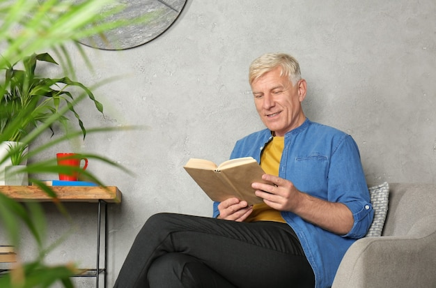 Attraktiver reifer mann, der buch drinnen liest
