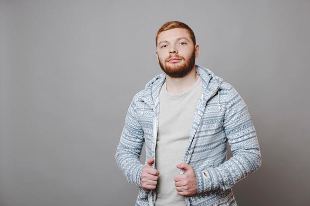 Attraktiver rotbärtiger mann im gemusterten kapuzenpulli, der kamera mit ernstem gesichtsausdruck beim stehen auf grauem hintergrund betrachtet