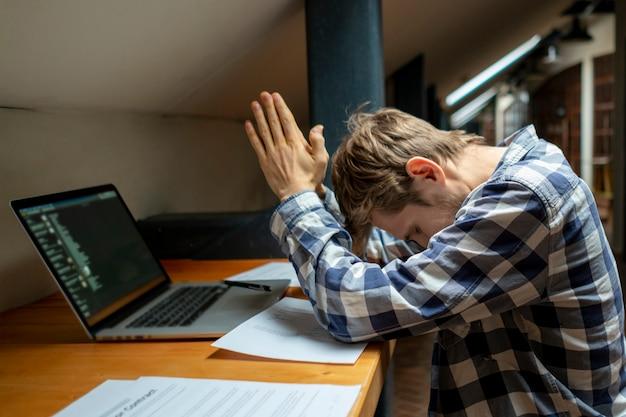 Attraktiver ruhiger starker mann, der während der pause auf seinem workplase meditiert
