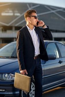 Attraktiver schöner geschäftsmann mit diplomat, der auf smartphone nahe dem auto spricht