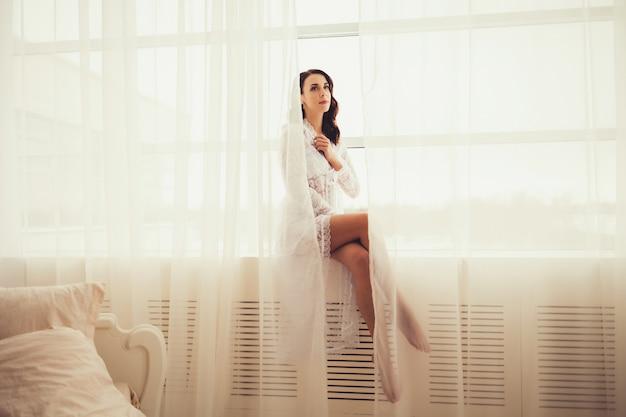 Attraktiver sexy brunette in der weißen kleideraufstellung