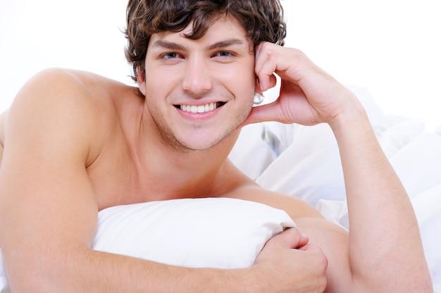 Attraktiver sexy lächelnder junger nackter mann, der im bett mit kissen liegt