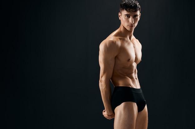 Attraktiver sportlicher mann in dunklen shorts, die dunkle wand phasenweise