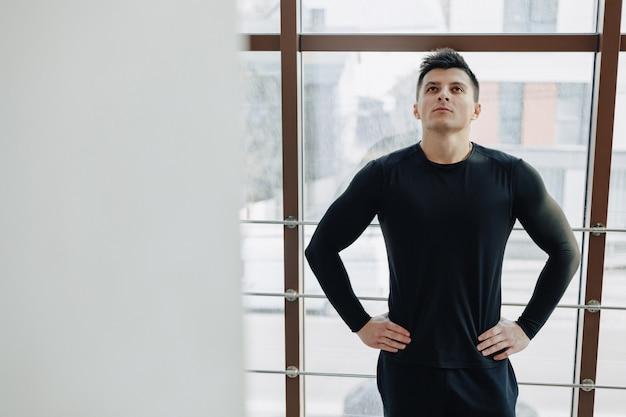 Attraktiver sportlicher typ am fenster. athlet posiert in der nähe von geräumigen fenstern. fitnessstudio und sport.