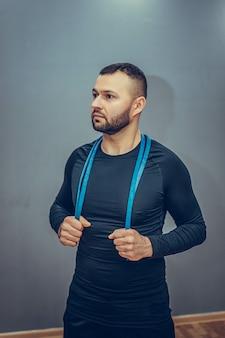 Attraktiver sportmann in der stilvollen sportbekleidung, die hände mit gummiband während des trainings auf grauem hintergrund streckt.