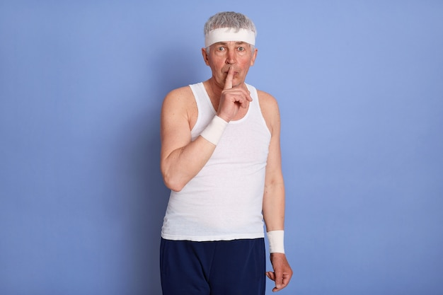 Attraktiver stilvoller älterer mann, der weißes ärmelloses t-shirt trägt, leise geste tut, vorderfinger an seinen lippen hält, bittet, sein geheimnis zu bewahren, posiert.