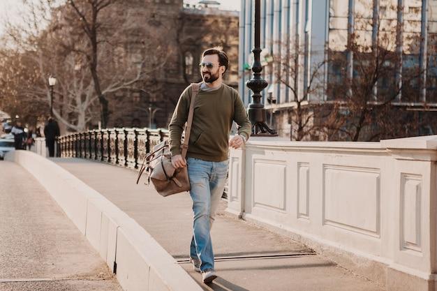 Attraktiver stilvoller hipster-mann, der in der stadtstraße mit ledertasche geht, die sweatshot und sonnenbrille trägt, stadtstil-trend, sonniger tag