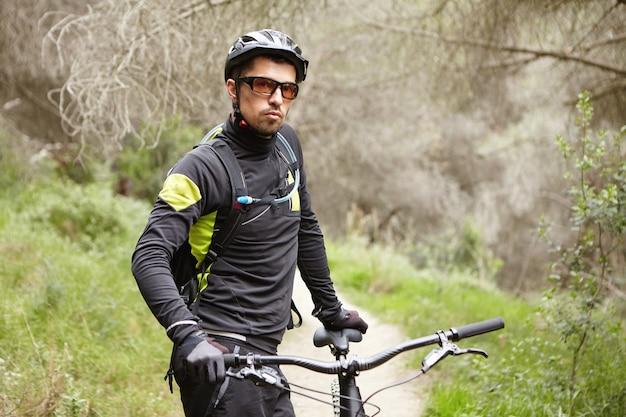 Attraktiver stilvoller männlicher biker, der schwarze fahrradkleidung, brille und helm stehend trägt
