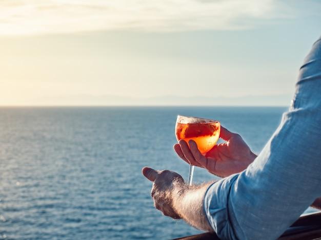 Attraktiver, stilvoller mann in der sonnenbrille, ein glas schönes rosa cocktail anhalten