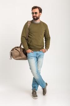 Attraktiver stilvoller mann reisender isoliert stehend mit tasche schön in jeans und sweatshot gekleidet